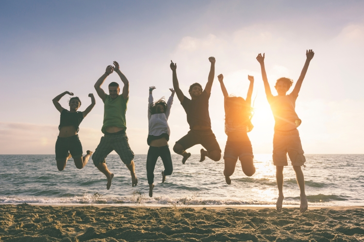 Multiracial Group of People Jumping at Beach, Backlight
