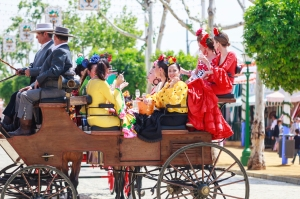 "Seville, Spain - April 28, 2015: Young and beautiful women on a horse drawn carriage during the the April Fair of Seville. The Seville Fair ""Feria de abril de Sevilla"" is one of most important celebration of the city, it begins one or two week after easter Holy Week, and is a big party where you can see women with traditional flamenco dress, beautiful horses, traditional carriages, dance Sevillanas, eat great tapas and drink liquors of the area"